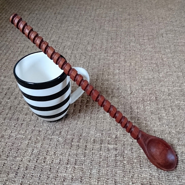 A handcarved wooden spoon in sapele wood with a barley twist detailed handle